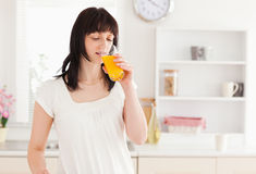 Lovely brunette drinking a glass of juice Royalty Free Stock Image