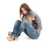 Lovely brunette in fur and jeans posing Royalty Free Stock Photography