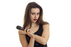 Lovely brunette girl with microphone in her hands looks at the camera Royalty Free Stock Photography