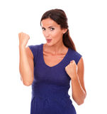 Lovely brunette girl in purple dress with arm up. As a sign of celebrating victory while looking at you smiling in white background Stock Image