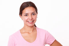 Lovely brunette girl smiling at you. Portrait of lovely brunette girl on pink t-shirt smiling at you on isolated white background Stock Photography