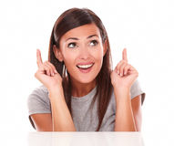 Lovely brunette pointing and looking up Stock Image