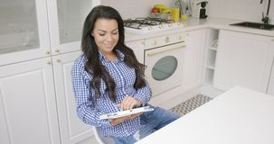 Lovely brunette sitting in kitchen with tablet stock video footage