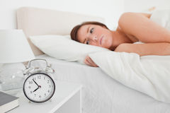 Lovely brunette woman awaking. With a clock while lying on a bed royalty free stock photo