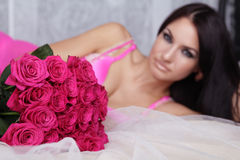 Lovely brunette woman with bouquet of pink roses lying on the be Stock Photos