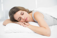 Lovely brunette woman napping lying on her bed Stock Image