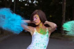 Lovely brunette woman with short hair posing with exploding Holi Stock Image