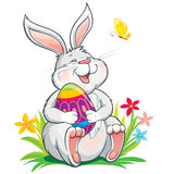Lovely  bunny sitting on grass and holding painted easter egg Stock Photography