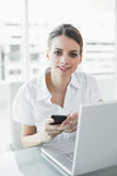 Lovely businesswoman holding her smartphone smiling softly at camera Stock Images