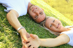 Lovely Caucasian Couple Smiling And Relax On Grass Stock Images