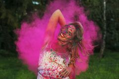 Lovely caucasian model with curly hair posing in a cloud of pink. Lovely caucasian woman with curly hair posing in a cloud of pink dry paint, celebrating Holi royalty free stock photo