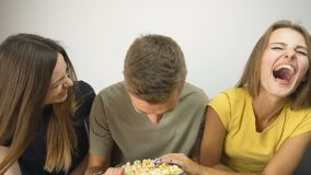 Lovely teens watch comedy. Lovely caucasian teens watch a rally funny comedy, eating popcorn on the comfortable grey sofa, slow motion stock footage