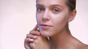 Lovely caucasian woman is touching her pure face carrying, isolated in white studio.  stock footage