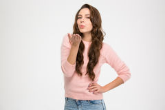 Lovely charming young woman in pink sweatshirt sending a kiss Stock Photo