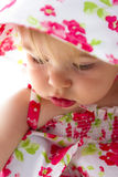 Lovely Cheeks. Baby looking deeply with her lovely cheeks and red lips with red flower dress Royalty Free Stock Photography