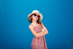 Lovely cheerful little girl in sunglasses standing with arms crossed Royalty Free Stock Photography