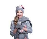 Lovely cheerful teenage girl wearing fuzzy sweater, scarf, mittens and hat isolated on white background. Winter clothes. Stock Photo