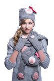 Lovely cheerful teenage girl wearing fuzzy sweater, scarf, mittens and hat isolated on white background. Winter clothes. Royalty Free Stock Photo