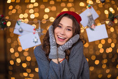 Lovely cheerful woman posing over handmade decoration and glittering background Stock Image