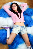 Lovely cheerleader. Wearing pink sweater and jeans shorts relaxing on the pom-poms Stock Images