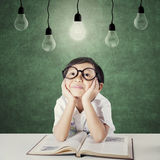 Lovely child with book looking up at lamp Royalty Free Stock Photo