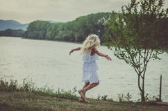Lovely child dancing at the lake royalty free stock images