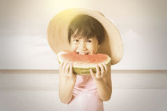 Lovely child enjoy a watermelon at coast Royalty Free Stock Image