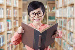 Lovely child with glasses holding book in library Royalty Free Stock Photography