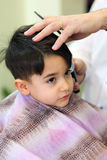 Lovely child at hairdresser. A lovely child in the hairdresser salon cutting his hair Stock Photo