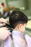 Lovely child at hairdresser. A lovely child in the hairdresser salon cutting his hair Stock Image