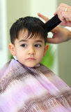 Lovely child at hairdresser. A lovely child in the hairdresser salon cutting his hair Royalty Free Stock Image