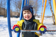 Lovely child in overall on climber in winter Stock Image