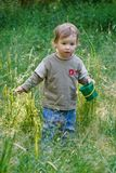 Lovely child plays to a grass royalty free stock photos