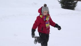 Lovely child running happy in the snow, season of white childhood joy. UHD 4K stock footage
