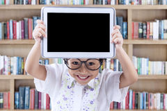 Lovely child showing tablet in the library Royalty Free Stock Images