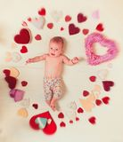 Lovely child. Small girl among red hearts. Love. Portrait of happy little child. Sweet little baby. New life and birth stock photo