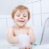 Lovely child splashing and playing with foam Royalty Free Stock Photos
