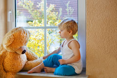 Lovely child of two years sitting near window with big toy bear. Stock Images