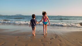 Boy and girl walking on the beach holding hands. Lovely children boy and girl walking on the beach holding hands. Slow motion stock footage