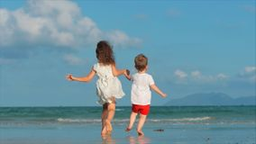 Lovely Children, Girl and a Boy Holding Hands Each Other Running Along the Tropical Coast to the Ocean. Concept stock video footage