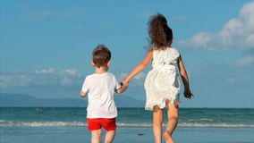 Lovely children, girl and a boy holding hands each other running along the tropical coast to the ocean. Concept stock footage