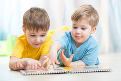 Lovely children reading a book, on the floor at Royalty Free Stock Photos