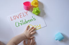 LOVELY Children's Day. Paper with inscription: LOVELY Children's Day, with child's hands, with colored blocks Royalty Free Stock Image