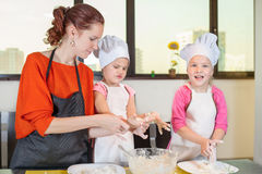 Lovely children together with mother preparing a cake Stock Photo