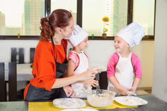 Lovely children together with mother preparing a cake Stock Photography