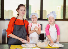 Lovely children together with mother preparing a cake Stock Image