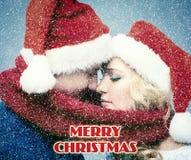 Lovely christmas couple in Santa Claus hats Stock Photos