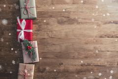 Lovely Christmas holiday creative border design idea background. With gift boxes and snow falling on wood table - top view royalty free stock image