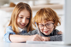 Lovely committed girl teaching her brother to write Royalty Free Stock Photo