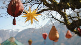 The lovely composition of the paper figures hanging on the tree at the background of the mountains. The lovely composition of the paper figures hanging on the stock footage